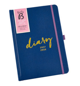 A blue ruled-line mid-year diary for 2017, with pockets for notes, faux leather cover, and pink strap to close it