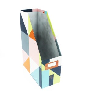 front shot of the geometric magazine rack, grey inside and with grey, blue, pink and green colours
