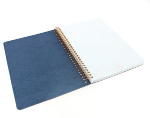 the wiro notebook features a blue geometric pattern inside the notebook and white lined paper and a gold wire binding