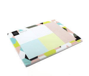 angled view of a lovely desk pad with a geometric design including various colours like blue, grey, green and pink